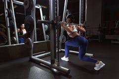 Den nätta unga kvinnan gör squats med skivstången i den utbildande apararusen i idrottshall royaltyfria bilder