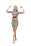 Den nätta unga kvinnan i grå färger klär isolerat på vit Arkivfoton