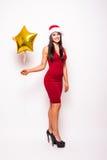 Den nätta unga kvinnan i röd klänning och santa julhatt med den guld- stjärnan formade ballongen Royaltyfria Foton