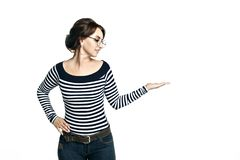 Den nätta unga kvinnan i randig åtsittande blus och runda exponeringsglas visar att peka handgesten som isoleras på vit bakgrund arkivbilder