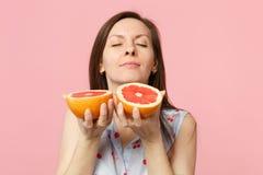 Den nätta unga kvinnan i sommarkläder som håller ögon, stängde sig och att sniffa halfs av den nya mogna grapefrukten som isolera royaltyfri bild