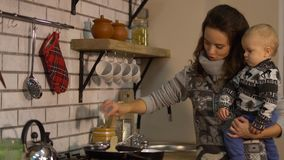 Den nätta unga kvinnan med behandla som ett barn i hennes armar i modernt kök som förbereder frukostdamen, häller saltar in i ste stock video
