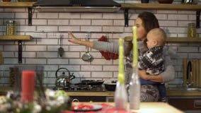 Den nätta unga kvinnan med behandla som ett barn i hennes armar i modernt kök som förbereder frukostfadern, skriver in köket med  arkivfilmer