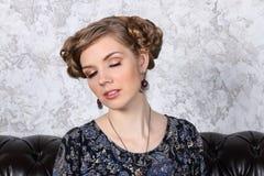 Den nätta unga kvinnan med frisyren poserar med bokslutögon Arkivbild