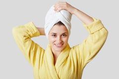 Den nätta unga kvinnan med handduken på huvudet, iklädd badrock, känner sig ny och avkopplad ater som tar duschen som isoleras öv Royaltyfri Foto