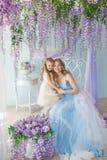Den nätta unga kvinnan med hennes lilla dotter sitter i en studio dekorerade blommor för en lila royaltyfria bilder