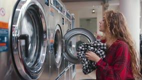 Den nätta unga kvinnan med rött lockigt hår satte kläder in i tvagningmashinen i tvätterit Iklädd tartanskjorta och lager videofilmer