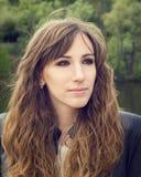 Den nätta unga kvinnan med smokeyögon utgör att posera nära floden royaltyfria foton