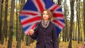 Den nätta unga kvinnan och hon behandla som ett barn att gå med britt flagga-som paraplyet i höst parkerar gränden skott för stea lager videofilmer