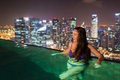 Den nätta unga kvinnan simmar på den oändliga pölen på taket arkivfoto
