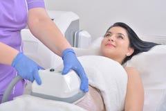 Den nätta unga kvinnan som får cryolipolyse fet behandling låtsas in royaltyfria bilder