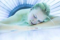 Den nätta unga kvinnan som garvar hennes hud i en modern solarium ska göra det Arkivfoton