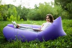 Den nätta unga kvinnan som ligger på uppblåsbar soffalamzacbläddrande i internet på bärbara datorn, medan vila på gräs, parkerar  arkivfoto