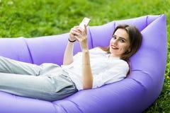Den nätta unga kvinnan som ligger på uppblåsbart soffalamzacbruk app från telefonen, bläddrandeinternet, medan vila på gräs, park arkivbild