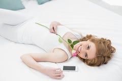 Den nätta unga kvinnan som vilar i säng med, steg Royaltyfri Bild