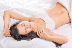 Den nätta unga kvinnan sover i säng Royaltyfri Foto