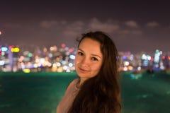 Den nätta unga kvinnan står på taket av Marina Bay Sands royaltyfri bild