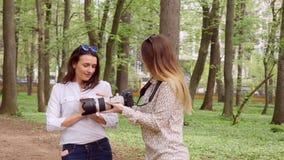 Den nätta unga kvinnan tycker om staden parkerar, leenden lager videofilmer