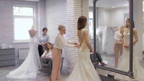 Den nätta unga kvinnan väljer en bröllopsklänning i shoppa, och shoppaassistenten hjälper henne Grupp av flickor in arkivfilmer