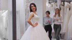 Den nätta unga kvinnan väljer en bröllopsklänning i shoppa, och shoppaassistenten hjälper henne Grupp av flickor in lager videofilmer