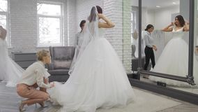 Den nätta unga kvinnan väljer en bröllopsklänning i shoppa, och shoppaassistenten hjälper henne Grupp av flickor in stock video