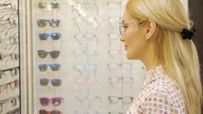 Den nätta unga kvinnan väljer exponeringsglas i optikerlager arkivfilmer