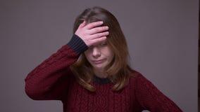 Den nätta unga kvinnliga studenten täcker framsidan med handen som gör en gest facepalm för att visa retning på grå bakgrund stock video