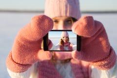 Den nätta unga kvinnliga turisten tar selfie i vinter Royaltyfria Bilder