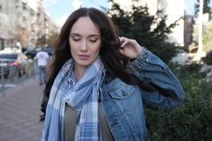 Den nätta unga kvinnlign i jeanslag poserar i en stadsgata Arkivfoto