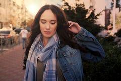 Den nätta unga kvinnlign i jeanslag poserar i en stadsgata Royaltyfria Foton