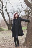 Den nätta unga moderna kvinnan i svart lag- och klänningställning vid trädet parkerar in vinterdag arkivfoto