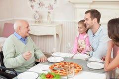 Den nätta vänliga familjen äter middag i kafé royaltyfri bild