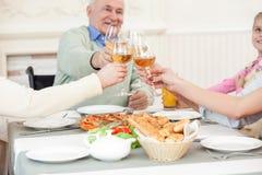 Den nätta vänliga familjen har en matställe hemma Fotografering för Bildbyråer