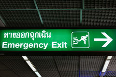 Den nöd- utgången undertecknar in engelskt och thai språk Arkivbild