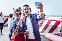 Den nöjda gruppen parar ihop att göra selfiebilden på kamera arkivbild