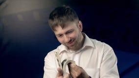 Den nöjda unga mannen är glad att få en stor packe av pengar lager videofilmer
