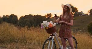 Den n?tta gulliga flickan som anv?nder smartphonen bredvid hennes cykel i parkera med, g?mma i handflatan p? en solig dag N?tt fl arkivfilmer