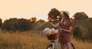 Den n?tta gulliga flickan som anv?nder smartphonen bredvid hennes cykel i parkera med, g?mma i handflatan p? en solig dag N?tt fl lager videofilmer