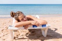 Den n?tta kvinnan solbadar p? sunbed p? stranden och har att le framsidan som g?ras av sunblock p? hennes hand royaltyfria foton
