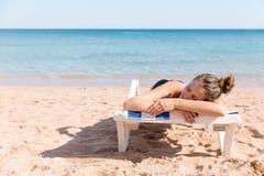 Den n?tta kvinnan solbadar p? sunbed p? stranden och har att le framsidan som g?ras av sunblock p? hennes hand royaltyfri fotografi