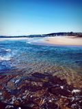 Den Narrabeen stranden med vaggar i NSW Australien Royaltyfri Foto
