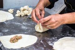 Den nationella georgiska kocken för bakgrund för kokkonstKhinkali metall förbereder gatan fo för maträtten för deg för rått kött  royaltyfri bild