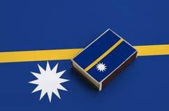 Den Nauru flaggan föreställas på en tändsticksask som ligger på en stor flagga arkivfoto