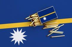 Den Nauru flaggan visas på en öppen tändsticksask, som flera matcher faller från och lögner på en stor flagga royaltyfria foton
