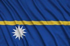 Den Nauru flaggan visas på ett sporttorkduketyg med många veck Baner för sportlag arkivfoto