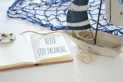 den nautiska begreppsbilden med vitt dekorativt seglar fartyget och öppnar anteckningsboken: STOPPA ALDRIG ATT DRÖMMA Royaltyfri Foto