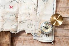 Den nautiska kompasset med fejkar skattöversikten av den abstrakta ön med Röda korset på trätabellen Arkivfoton