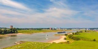 Den Nederrijn floden framme av den holländska staden av Arnhem Arkivfoto