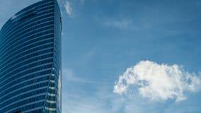 Den nedersta övre sikten av en skyskrapa och den blåa himlen och ett moln, zoomar in stock video