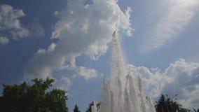 Den nedersta sikten av vattenstrålar från springbrunnen flyger upp mot gränslös blå himmel med flyttning som vita moln i stad par lager videofilmer